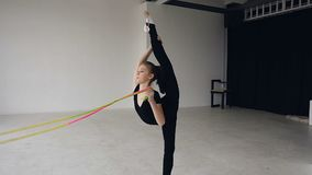 Gymnastic school and energy. Girl gymnast in black sportswear with rope in split. Flexibility in acrobatics and fitness. Health. Workout of girl on gymnastick stock video