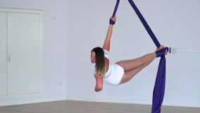 Gymnastic youn woman makes aerial silks perfomance stock video footage