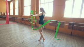 Gymnastic - young woman dancing with a green ribbon -training a gymnastics exercise, slow-motion. Shot, wide angle stock video footage