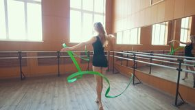 Gymnastic - young woman dancing with a green ribbon -training a gymnastics exercise, slow motion. Wide angle stock video