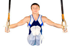 Gymnastics. The sportsman the guy, carries out difficult exercise, sports gymnastics, on white background, isolated Royalty Free Stock Photos