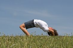 Gymnastics. Young pretty girl makes gymnastics on a green grass on a background of the blue sky stock image