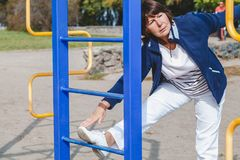 Elderly woman performs squatting on summer sports ground Royalty Free Stock Images