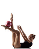 Gymnastics exercise with ball. Young woman doing gymnastics exercise over white background Stock Photo