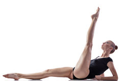 Gymnastics exercise. Young woman doing gymnastics exercise over white background Stock Photos
