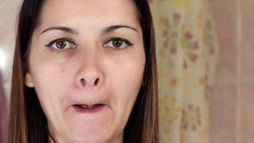 Gymnastics for a face, woman doing anti-aging exercises. Facebuilding facial exercises. Face yoga. girl looking in the stock video footage