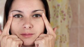 Gymnastics for a face, woman doing anti-aging exercises. Facebuilding facial exercises. Face yoga. girl looking in the stock footage