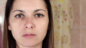 Gymnastics for a face, woman doing anti-aging exercises. Facebuilding facial exercises. Face yoga. girl looking in the stock video
