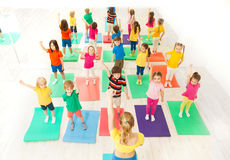 Gymnastics group session for kids in fitness class. Top view picture of gymnastics group session for kids with female instructor in gym Royalty Free Stock Photo