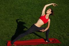 Gymnastics outdoors. beautiful girl doing stretching. Woman practices yoga in nature Royalty Free Stock Photography
