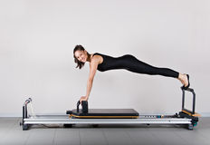 Gymnastics pilates. Reformer front support position. Pilates gymnastics is a Germanic evolution of yoga, used by athletes to improve flexibility and body fitness Royalty Free Stock Images