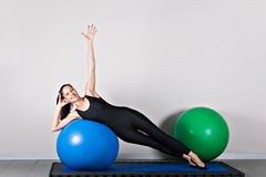 Gymnastics pilates. Side bend  with ball position. Pilates gymnastics is a Germanic evolution of yoga, used by athletes to improve flexibility and body fitness Royalty Free Stock Photo