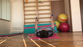 Gymnastics room. Young man doing a set of exercises with dumbbells. stock footage
