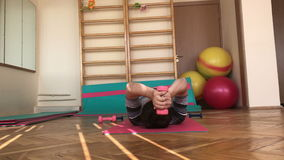 Gymnastics room. Young man doing a set of exercises with dumbbells. stock video footage