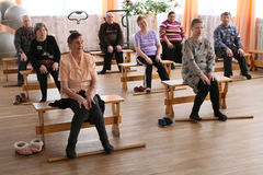 Gymnastics with sticks for eldery. Day of Health in Center of social services for pensioners and the disabled Otrada in Podporozhye, Russia Stock Photo