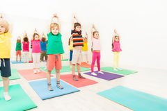 Gymnastics workshops for kids in sport club. Group of 5-6 years old kids standing on yoga mats with their hands up during gymnastics in sport club Stock Photography