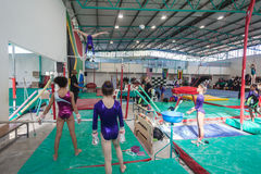 Gymnastics Young Parallel Bars. Gymnastics young girls warm up on the parallel bars apparatus swinging with coach assistance under bar.Photo action image behind Royalty Free Stock Images