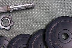 Gymnastiek harde domoor en gewichten Het materiaal van de Stelsport op de vloerachtergrond van de metaalgymnastiek Stock Afbeelding