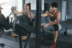 Gymnastiek Man en Vrouwen Opleiding op het Roeien Machine bij Crossfit-Club stock afbeeldingen