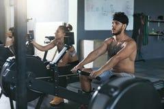 Gymnastiek Man en Vrouwen Opleiding op het Roeien Machine bij Crossfit-Club royalty-vrije stock afbeelding