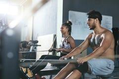 Gymnastiek Man en Vrouwen Opleiding op het Roeien Machine bij Crossfit-Club stock foto's