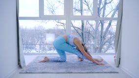 Gymnastik böjlig kvinna som gör sträckning nära panorama- fönster på konditionklubban arkivfilmer