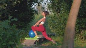 Gymnastik in der Natur, aktive schöne weibliche Ausführungsausdehnende Übung während des Eignungstrainings draußen auf hölzernem stock video footage