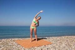 Gymnastik på stranden vid havet Royaltyfria Bilder