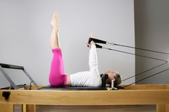 Gymnastikfrau pilates, die Sport im Reformerbett ausdehnen Stockbilder