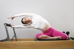 Gymnastikfrau pilates, die Sport im Reformerbett ausdehnen Lizenzfreies Stockfoto