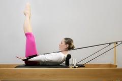 Gymnastikfrau pilates, die Sport im Reformerbett ausdehnen Stockfotografie