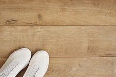 Gymnastikskor för vita kvinnor på en träbakgrund Lägenhet som är lekmanna- av moderna vita skor Över huvudet fotografi för bästa  royaltyfri foto