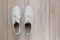 Gymnastikskor för vitt läder på träbakgrund royaltyfria foton