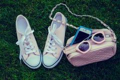 Gymnastikskor, mobiltelefon, handväska och solglasögon Royaltyfria Bilder