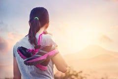 Gymnastikskor på skuldras kvinna som ska tyckas om fotvandra och koppla av på berget i soluppgång royaltyfri fotografi