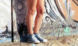 Gymnastikskor som är slitna vid flickaanseendet nära väggen med grafitti Royaltyfri Fotografi