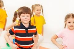 Gymnastique de pratique de garçon heureux dans le jardin d'enfants Images stock
