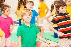 Gymnastique de pratique de garçon mignon chez le groupe du ` s des enfants Images libres de droits