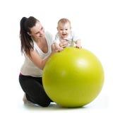 Gymnastique pour le bébé avec la boule de forme physique Photographie stock libre de droits