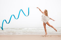 Gymnastkvinnadans med bandet på stranden royaltyfri bild