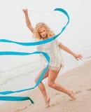 Gymnastkvinnadans med bandet på stranden royaltyfria foton