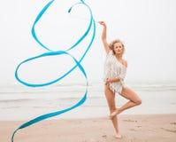 Gymnastkvinnadans med bandet på stranden arkivfoton