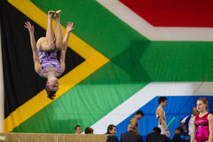 Gymnasts Girl Air Somersault Beam. Gymnast girl beam air flip somersault program before judges during the competition at South African National champs.Close-up Royalty Free Stock Image