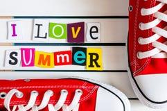 Gymshoes rouge et moi aiment l'été - écrit avec des coupures de lettre de magazine de couleur sur le conseil en bois Concept de v Photographie stock