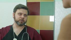 Gynäkologedoktor, der mit schwangerer Frau am Krankenhaus spricht stock footage