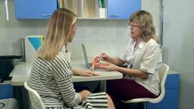 Gyn?kologe, der weibliches Geb?rmutteranatomiemodell h?lt und mit Patienten spricht stock footage