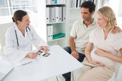 Gynaecologist explaining reports to expectant couple Stock Image