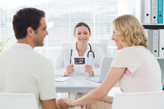 Gynaecologist looking at expectant couple Stock Photos