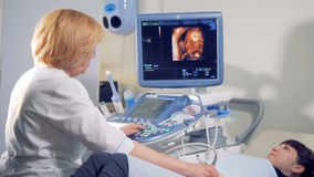 Gynecologist is carrying out an ultrasound procedure on a female patient. 4K stock video