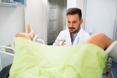 Gynecologist examination his patient. Beautiful young women lying in gynecology clinic doing examination, gynecologist check up exam royalty free stock images